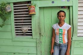 dominican republic woman in front of house